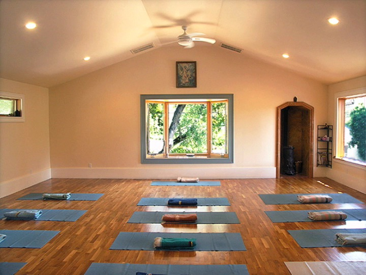 Photo of empty studio with yoga mats and blankets placed throughout.